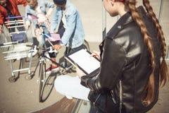 Vista posterior de la muchacha del adolescente que usa la tableta digital en parque del monopatín Fotografía de archivo