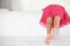 Vista posterior de la muchacha que juega en el sofá fotografía de archivo libre de regalías