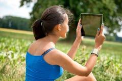 Vista posterior de la muchacha que usa una tableta que se sienta en prado Foto de archivo