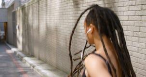 Vista posterior de la mujer afroamericana que activa en la ciudad 4k almacen de video