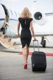 Vista posterior de la mujer con equipaje que camina hacia Imagen de archivo