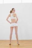 Vista posterior de la mujer delgada hermosa que presenta en pasillo de deportes Foto de archivo libre de regalías