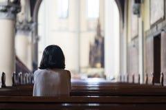 Vista posterior de la mujer devota que ruega en la iglesia imagenes de archivo