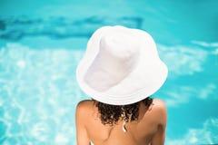 Vista posterior de la mujer en el sombrero blanco que se sienta cerca de piscina Fotografía de archivo libre de regalías