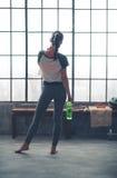 Vista posterior de la mujer en engranaje del entrenamiento en el gimnasio del desván que sostiene el agua Fotos de archivo libres de regalías