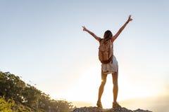Vista posterior de la mujer joven emocionada con la mochila que se coloca en el top de la colina con sus brazos extendidos Mujer  imágenes de archivo libres de regalías
