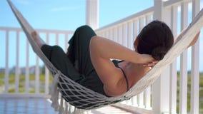 Vista posterior de la mujer joven que disfruta de un día soleado en la hamaca en su terraza metrajes