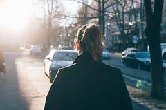 Vista posterior de la mujer joven que lleva la capa negra Foto de archivo libre de regalías