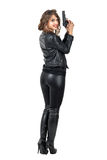 Vista posterior de la mujer peligrosa atractiva que lleva a cabo una cabeza de la vuelta del arma y que sonríe en la cámara Fotos de archivo libres de regalías