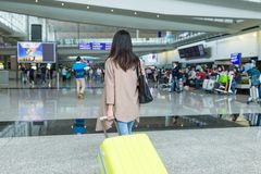 Vista posterior de la mujer que camina con equipaje en el international de Hong Kong Foto de archivo libre de regalías