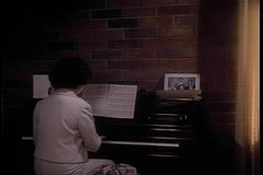 Vista posterior de la mujer que juega el piano almacen de metraje de vídeo