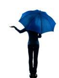 Vista posterior de la mujer que lleva a cabo gesto de la palma del paraguas Foto de archivo