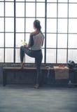 Vista posterior de la mujer que mira hacia fuera la ventana que sostiene el agua en gimnasio del desván Foto de archivo