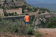 Vista posterior de la opinión de fotografía del hombre de las montañas de Montserrat y de la abadía benedictina de Santa Maria de Foto de archivo