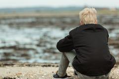 Vista posterior de la persona rubia que se sienta en la playa rocosa Imagen de archivo libre de regalías