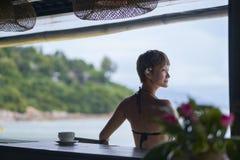 Vista posterior de la sentada asiática joven de la belleza, relajándose en la barra de la playa en vacaciones foto de archivo