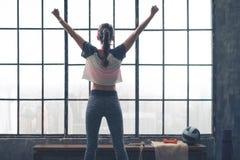 Vista posterior de la ventana que hace una pausa de la mujer del júbilo en gimnasio del desván Fotografía de archivo libre de regalías