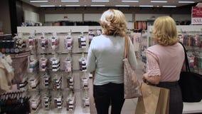 Vista posterior de las mujeres que caminan en tienda de ropa almacen de metraje de vídeo