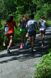 Vista posterior de los adolescentes que corren en la trayectoria 2 Foto de archivo