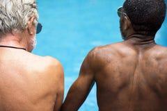 Vista posterior de los adultos mayores diversos que se sientan por el goce de la piscina Imagen de archivo libre de regalías