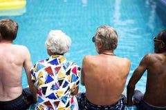 Vista posterior de los adultos mayores diversos que se sientan por el goce de la piscina foto de archivo