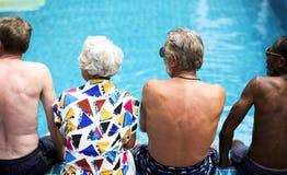 Vista posterior de los adultos mayores diversos que se sientan por la piscina que disfruta del verano junto fotografía de archivo