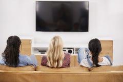 Vista posterior de los amigos femeninos que se sientan en Sofa Watching Television imagen de archivo
