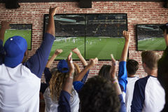 Vista posterior de los amigos que miran el juego en la celebración de la barra de deportes fotografía de archivo