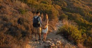 Vista posterior de los caminantes del hombre y de la mujer que emigran una trayectoria rocosa en el lado de la colina Naturaleza  foto de archivo libre de regalías