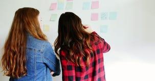 Vista posterior de los ejecutivos de sexo femenino que escriben en notas pegajosas