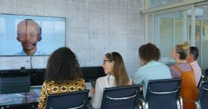 Vista posterior de los ejecutivos de operaciones de la raza mixta que hacen videoconferencia en la oficina moderna 4k metrajes