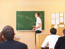 Vista posterior de los estudiantes atento que escuchan el estudiante masculino Fotografía de archivo
