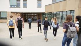 Vista posterior de los estudiantes de la escuela secundaria que caminan en la universidad que construye junto fotografía de archivo libre de regalías
