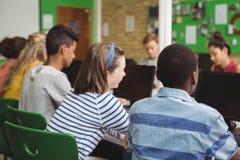 Vista posterior de los estudiantes que estudian en sala de clase del ordenador Fotos de archivo libres de regalías
