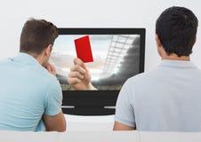 Vista posterior de los hombres que miran la televisión en sala de estar Imágenes de archivo libres de regalías