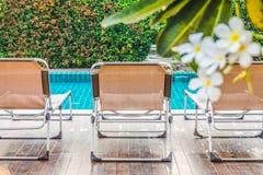 Vista posterior de los ociosos de aluminio del sol en cubiertas en el lado de la piscina fotos de archivo