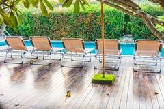 Vista posterior de los ociosos de aluminio del sol en cubiertas de madera en el lado de la piscina fotos de archivo