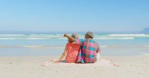 Vista posterior de los pares afroamericanos mayores activos que se relajan en la manta en la sol en la playa 4k almacen de metraje de vídeo