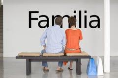 Vista posterior de los pares asentados en el banco que lee el texto español Familia (familia) en la pared Fotos de archivo