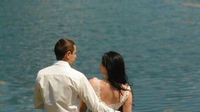 Vista posterior de los pares atractivos de los recienes casados que besan y que disfrutan del paisaje marino metrajes