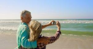 Vista posterior de los pares caucásicos mayores activos que toman el selfie con el teléfono móvil en la playa 4k almacen de metraje de vídeo
