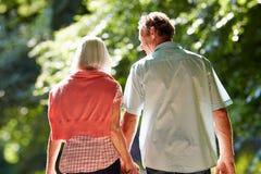 Vista posterior de los pares envejecidos centro que caminan a lo largo de carril del país Foto de archivo libre de regalías