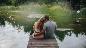 Vista posterior de los pares felices que se sientan en un lago imagen de archivo libre de regalías