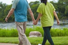 Vista posterior de los pares jovenes que caminan llevando a cabo las manos Imágenes de archivo libres de regalías