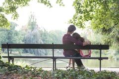 Vista posterior de los pares jovenes románticos que se sientan en banco en la orilla del lago Imagenes de archivo