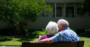 Vista posterior de los pares mayores caucásicos activos que miran el álbum de foto en el jardín de la clínica de reposo 4k almacen de video