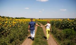 Vista posterior de los pares que caminan en campo del verano foto de archivo