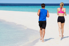 Vista posterior de los pares que corren en la playa hermosa Imagenes de archivo