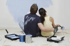 Vista posterior de los pares que miran la pintura en la pared Imágenes de archivo libres de regalías