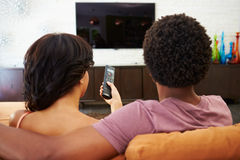 Vista posterior de los pares que se sientan en Sofa Watching TV junto Fotografía de archivo libre de regalías